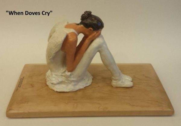 Ceramic ballerina sitting and crying with her face buried in her hands,