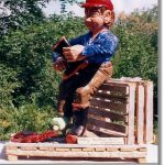 A fisherman sitting on a crate patches his boot